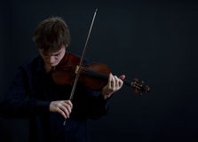 Teen Violinist. Virtuoso Teen Male Violinist on Dark Background bowed Stock Photos