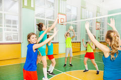Teen volleyball players having match in gymnasium Stock Photo