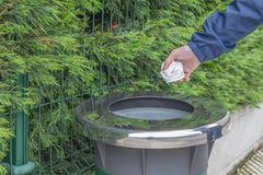 Teen volunteer in a blue jacket windbreaker throws collected plastic trash in a container stock images