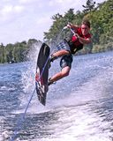 Teen on wakeboard. Teen wakeboarding and doing tricks in the lake Royalty Free Stock Photo