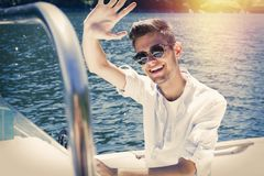 Teen waving from boat in golden sunlight. Closeup of a smiling male teen waving as he is driving a boat in a waterway with golden sunlight behind him on the Stock Photos