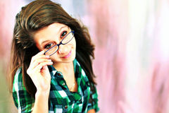 Teen wearing glasses. A pretty teenage girl wearing glasses peeking over them Royalty Free Stock Photography