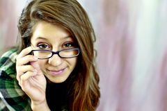 Teen wearing glasses. A pretty teenage girl wearing glasses peeking over them Stock Photography
