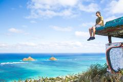 Young man sitting on pillbox over looking Lanikai looking out over the Pacific Ocean loving sitting on top of the world. Teen wearing a hat sitting on pillbox stock photography