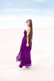 Teen wearing purple dress on beach looking back over shoulder Royalty Free Stock Photos
