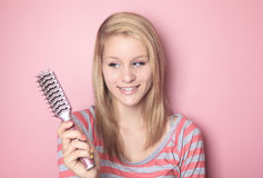 Teen who brushing her hair in her bedroom Royalty Free Stock Photo