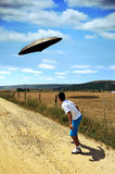 Close encounter. A teen who was walking close to the fields, afraid by the appearance of a flying saucer stock illustration
