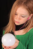 Teen witch 3. Teenage girl with green shirt holding a crystal ball with ipod Royalty Free Stock Image