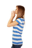 Teen woman with allergy or cold blowing nose Royalty Free Stock Image