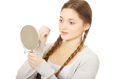 Teen woman applying lipstick looking at mirror. Royalty Free Stock Images