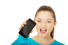 Teen woman with a broken cell phone. Teen woman with a broken cracked phone screen stock images
