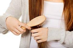 Teen woman brushing her hair. stock photos
