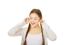 Teen woman covering ears with fingers. Stock Photos