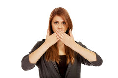 Teen woman covering her mouth with both hands.  stock photos