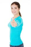 Teen woman gesturing thumbs up Stock Photo