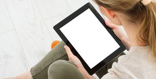 Teen woman girl using a tablet pc sitting on the floor in a living room , touching blank screen stock photo