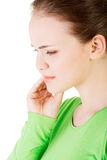 Teen woman having a terrible tooth ache. Teen woman pressing her bruised cheek with a painful expression as if she's having a terrible tooth ache Royalty Free Stock Images
