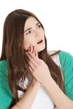Teen woman having a terrible tooth ache. Teen woman pressing her bruised cheek with a painful expression as if she's having a terrible tooth ache Royalty Free Stock Photography