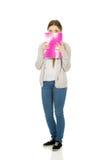 Teen woman hiding behind a notebook. Stock Photos