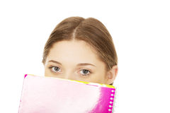 Teen woman hiding behind a notebook. Royalty Free Stock Images