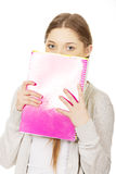 Teen woman hiding behind a notebook. Royalty Free Stock Photos