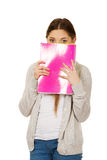 Teen woman hiding behind a notebook. Stock Photo
