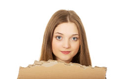 Teen woman holding cardboard sheet. Royalty Free Stock Images