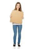 Teen woman holding cardboard sheet. Royalty Free Stock Photography