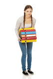 Teen woman holding heavy binders. Stock Images