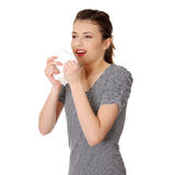 Teen woman holding tissue and sneezing. Isolated on white background Stock Images