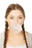 Teen woman making balloon with gum. Royalty Free Stock Images