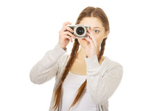 Teen woman making photo with camera. Royalty Free Stock Photos