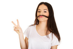 Teen woman putting hair like moustache. Stock Photography