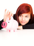 Teen woman putting money in piggy bank Stock Photography