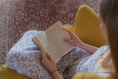Teen woman read book chair inside Royalty Free Stock Photography