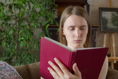 Teen woman read book chair inside Stock Photo
