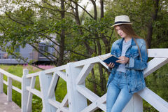 Teen woman read book outside. Person teenager read book study outside garden Stock Photos
