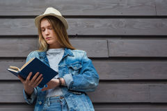 Teen woman read book outside wall Royalty Free Stock Photography