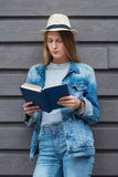Teen woman read book outside wall Stock Image
