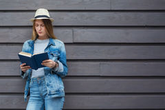 Teen woman read book outside wall. Person teenager read book study outside wall Stock Photo