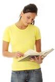 Teen woman reading book Stock Image