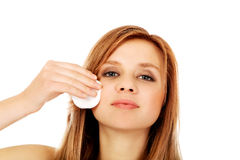Teen woman removing makeup with cotton pad Stock Image