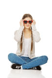 Teen woman sitting wearing sunglasses. Stock Photos