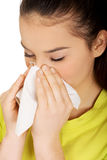 Teen woman sneezing to tissue. Stock Images