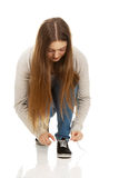 Teen woman tie shoes. Royalty Free Stock Images