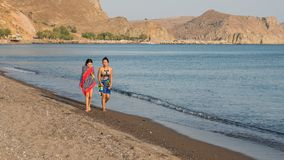 Teen and woman walking along beach with towels wrapped around th stock images