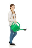 Teen woman with watering can. Royalty Free Stock Image