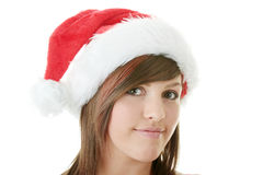 Teen woman wearing Santa hat. Beautiful young woman wearing Santa hat at Christmas isolated against white background Royalty Free Stock Image