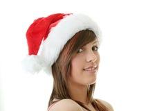 Teen woman wearing Santa hat. Beautiful young woman wearing Santa hat at Christmas isolated against white background Stock Photo