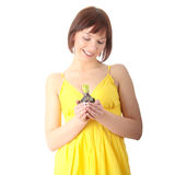 Teen woman in yellow dress holding small plant Stock Photography